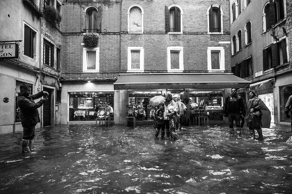 Venice, Italy. 29 October, 2018.  People take pictures in San Marco district during the high tide on October 29, 2018, in Venice, Italy. This is a selection of pictures of different areas of Venice that the press has not covered, were resident live and every year they have to struggle with the high tide. Due to the exceptional level of the 'acqua alta' or 'High Tide' that reached 156 cm today, Venetian schools and hospitals were closed by the authorities, and citizens were advised against leaving their homes. This level of High Tide has been reached in 1979. © Simone Padovani / Awakening / Alamy Live News