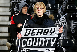 A Derby County fan in the stands waves a flag to show their support
