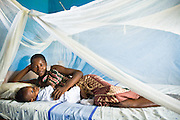 A woman and her child lie in bed under a treated mosquito net. Northern Ghana, Thursday November 13, 2008.
