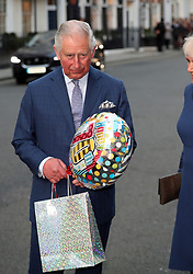 The Prince of Wales holds a birthday gift as he arrives for a tea party at Spencer House in London to celebrate 70 inspirational people marking their 70th birthday this year.
