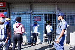 May 5, 2020 - Johannesburg, Gauteng, South Africa - SAPS constantly check if people are maintaining social distance while they line for the queue in front of a local shop. (Credit Image: © Manash Das/ZUMA Wire/ZUMAPRESS.com)