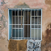 Clothes hang outside a window on the street in Santiago, Cuba. A pair of shorts is tattered almost beyond recognition.