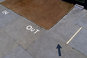 A detail view of In and Out markings clearly marked out on the ground, at the entrance and exit of a corporate address during the third lockdown of the Coronavirus  pandemic, in the City of London, the capital's financial district, on 10th February 2021, in London, England.