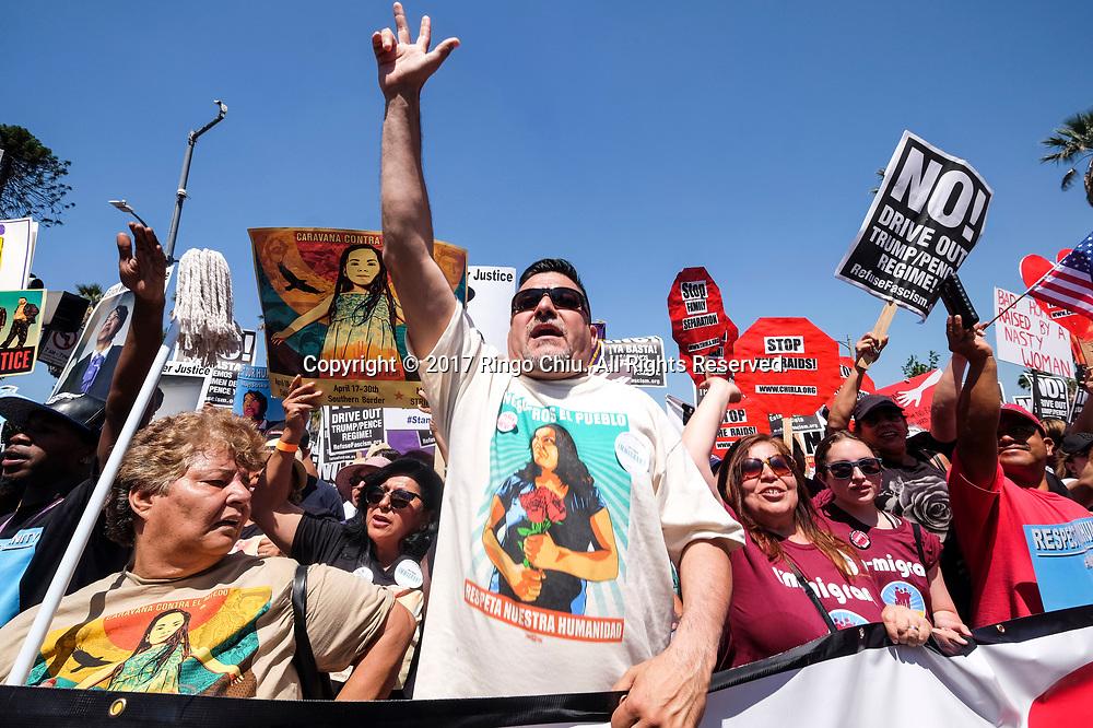 """5月1日,在美国洛杉矶,人们手持标语牌参加""""五一""""国际劳动节游行。 当日,全美各城市的数以万计移民及其支持者集会抗议特朗普总统的移民政策,为工人权益发声。新华社发(赵汉荣摄)<br /> Protesters carry signs marching toward downtown Los Angeles in the annual May Day March in Los Angeles, the United States, May 1, 2017. Thousands of people took to the streets across the nation Monday to march in May Day rallies, calling for immigration reform, workers' rights and police accountability. (Xinhua/Zhao Hanrong)(Photo by Ringo Chiu/PHOTOFORMULA.com)<br /> <br /> Usage Notes: This content is intended for editorial use only. For other uses, additional clearances may be required."""