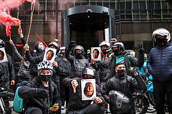 © Licensed to London News Pictures. 07/04/2021. LONDON, UK.  Deliveroo riders and drivers on strike stage a protest outside the company's headquarters in Cannon Street (holding Will Shu, CEO, facemasks) against the company demanding improvements to pay and conditions in terms of minimum wage, holidays and sick leave.  The strike comes on the same day that the company's shares are publicly traded for the first time following its initial public offering (IPO) on 31 March, where shares fell by 25% after failing to receive support by institutional investors who cited concerns about the company's policy on workers' rights.  Photo credit: Stephen Chung/LNP