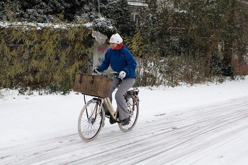 Een vrouw fietst op de Amsterdamseweg in Arnhem door de sneeuw.<br /> <br /> A woman is cycling at the Amsterdamseweg in Arnhem in the snow.