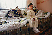 A three-and-a-half-year-old boy waits to be circumcised at his home in Istanbul, Turkey. He is younger than the usual circumcision age because his parents want him to undergo the ritual together with his older brother.  Custom dictates that boys are dressed up as small sultans or princes at their circumcision, and the cloaks and hats and sceptres of the two boys are scattered on the sofa on which the boy is sitting. The boy will be circumcised by a licensed circumciser.
