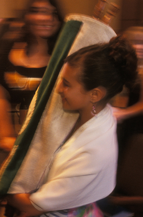 A Jewish girl performs her bat mitzvah, her coming of age ceremony, at Temple Avoda, a Reform synagogue, in Fair Lawn, New Jersey, USA. The girl carries the holy Torah scrolls through the synagogue  after reading extracts to the congregation. Jewish tradition dictates that a girl comes of age at twelve, though in Reform and Conservative Jewish congregations they usually become bat mitzvahs at thirteen, the same age as boys.
