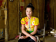 Portrait of a Vietnamese prostitute wearing traditional Tai Dam clothing and hairstyle at home in Ban Pakpok, Phongsaly province, Lao PDR. Ban Pakpok is small collection of houses recently relocated near to the Nam Ou river due to the Nam Ou Cascade Hydropower Project Dam 5. It is the closest habitation to the dam construction site, the local people rent rooms to the prostitutes who provide services to the Chinese construction workers.