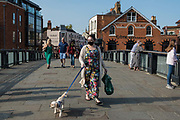 A woman walking a dog on Eton Bridge wears a face covering to help prevent the spread of the coronavirus on 19 September 2020 in Windsor, United Kingdom. The government is currently believed to be considering a short period of tighter rules across England to combat a rise in infections following confirmation by its scientific advisers that the number of new COVID-19 cases is doubling every week.