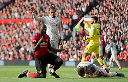 Liverpool's Andrew Robertson (right) lies injured on the pitch after clashing with Manchester United's Romelu Lukaku