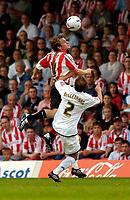 Photo: Catrine Gapper.<br /> Brentford v MK Dons. Coca Cola League 1.<br /> 10/09/2005.<br /> Jay Tabb brentford) taking a header over MK Dons McClenahan.