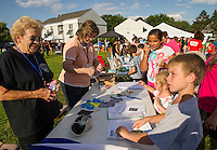 Volunteers Carole Veer and Corinne Merrill passed out information on the Civilian Academy and Victim Services programs to visitors at Laconia's National Night Out at Blueberry Lane Apartments on Tuesday evening.   (Karen Bobotas/for the Laconia Daily Sun)