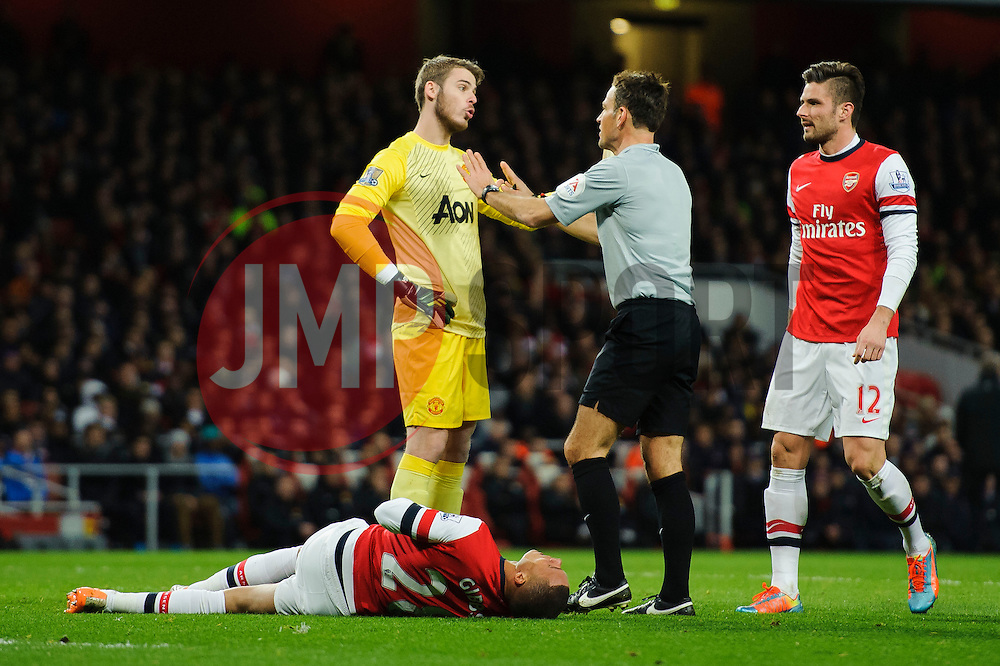 Man Utd Goalkeeper David De Gea (ESP) argues with referee Mark Clattenburg as Arsenal Defender Kieran Gibbs (ENG) lays on the ground after colliding with Man Utd Defender Rafael (BRA) - Photo mandatory by-line: Rogan Thomson/JMP - 07966 386802 - 12/02/14 - SPORT - FOOTBALL - Emirates Stadium, London - Arsenal v Manchester United - Barclays Premier League.
