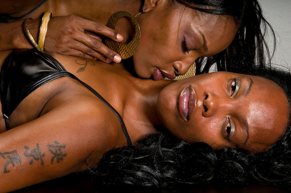 African American, lesbian couple in erotic foreplay game.