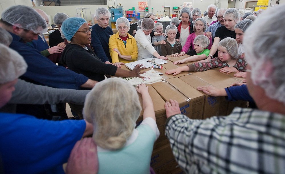 Volunteers finish one of several packing sessions by praying over the food they just packed, Friday, April 9.