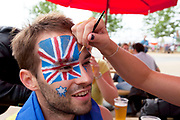 London 2012 Olympic Park in Stratford, East London. Australian fans apply a face paint flag to one of their friends.