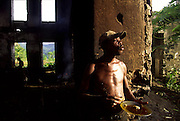 Man eating bread diped in palm oil. In the ruins of this former Roca (farm) palm oil is produced in a traditional way.