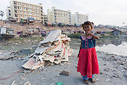 Young girl in red and blue, new towers in background, Mandalay