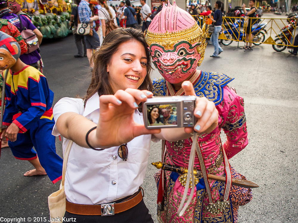 """14 JANUARY 2015 - BANGKOK, THAILAND:  An exchange student takes a """"selfie"""" of herself and a soldier in the Thai monkey army, a popular character from Thai mythology, during the 2015 Discover Thainess parade. The Tourism Authority of Thailand (TAT) sponsored the opening ceremony of the """"2015 Discover Thainess"""" Campaign with a 3.5-kilometre parade through central Bangkok. The parade featured cultural shows from several parts of Thailand. Part of the """"2015 Discover Thainess"""" campaign is a showcase of Thailand's culture and natural heritage and is divided into five categories that match the major regions of Thailand – Central Region, North, Northeast, East and South.    PHOTO BY JACK KURTZ"""