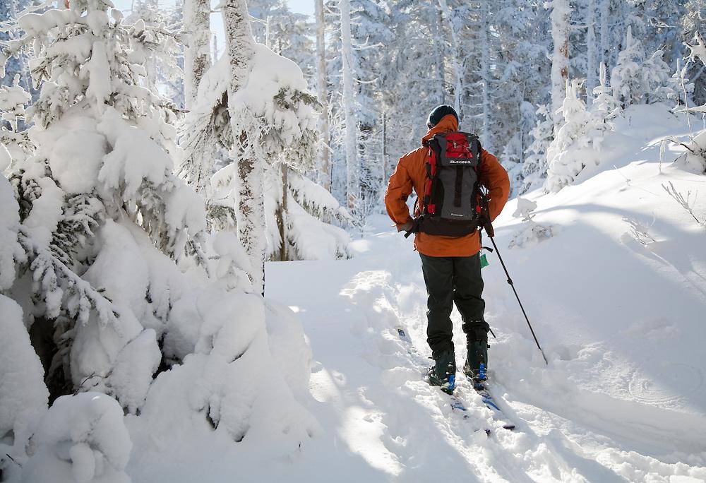 Backcountry telemark skier, Dennis Delena takes a break in the warm sun, Vermont.