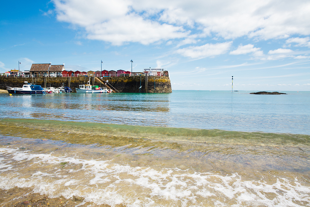 Crystal clear, calm water at Rozel harbour, Jersey looking across at the fishing boats, pier and the popular cafe The Hungry Man