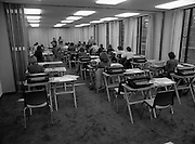 Conference Room at the EEC Building.   (N60)..1981..07.02.1981..02.07.1981..7th February 1981...At the EEC offices, 39 Molesworth Street, the conference room was converted to an examination hall for the purpose of recruiting staff..Image shows the room laid out with secretarial equipment as the applicants take their places for the exam.The invigilators hand out the test papers.
