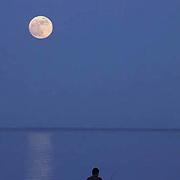 Lone fisherman steelhead fishing on Lake Superior. Moonlight evening. Minnesota.