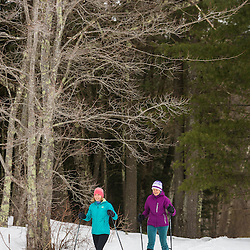 Two women snowshoe on a forest trail in Epping, New Hampshire.
