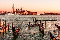 Gondolas ply the Venice Lagoon at sunset, Venice, Italy.