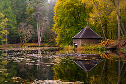 Pitlochry, Scotland, UK. 24th October 2021. Autumnal colours on trees and boathouse are reflected in Loch Dunmore near Pitlochry as seen from a drone. The forests and woods of Perthshire are ablaze with autumn colours at the moment.  Iain Masterton/Alamy Live News.