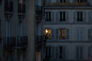 """Evening light from apartment rooms glowing on the rue Navarin, 9th Arrondissement, Paris, France. Seen from down the street in the district known affectionately as South Pigalle (aka """"SoPi"""") we see the glow of house lights in a room 3 or 4 floors up from street level. There is no-one home or nobody seen in the flat. It's late and the shutters are either open or closed in the blue light of a Parisien evening."""