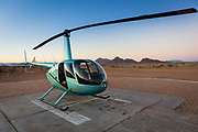"""Sightseeing helicopter in the Namib-Naukluft National Park in Namibia.<br /> <br /> Sossusvlei is a salt and clay pan surrounded by high red dunes, located in the southern part of the Namib Desert, in the Namib-Naukluft National Park of Namibia. The name """"Sossusvlei"""" is often used in an extended meaning to refer to the surrounding area (including other neighbouring vleis such as Deadvlei and other high dunes), which is one of the major visitor attractions of Namibia.<br /> <br /> The name """"Sossusvlei"""" is of mixed origin and roughly means """"dead-end marsh"""". Vlei is the Afrikaans word for """"marsh"""", while """"sossus"""" is Nama for """"no return"""" or """"dead end"""". Sossusvlei owes this name to the fact that it is an endorheic drainage basin (i.e., a drainage basin without outflows) for the ephemeral Tsauchab River."""