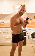 Young man shaving his head home haircut in kitchen, UK - model released