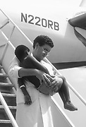 The Orbis Flying Eye Hospital : Recovery. Young boy carried frome the plane after surgery.