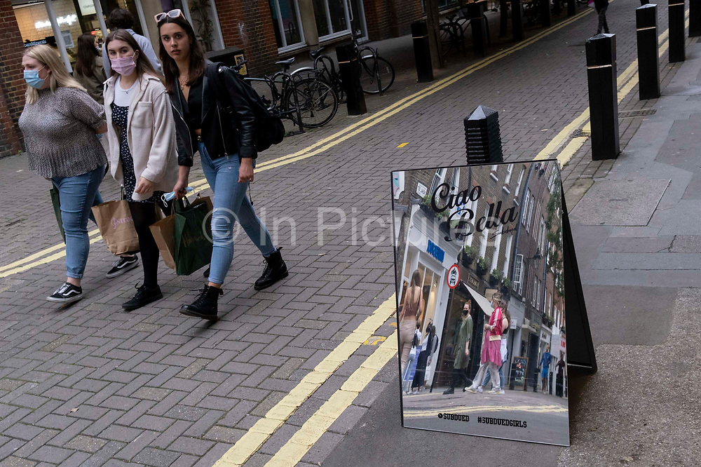 Women shoppers walk along Neal Street, passing-by a mirrored sign for fashion retailer Subdued, on 12th July 2021, in London, England. Subdued is an Italian brand .. for fun-loving, strong and independent teenagers. Founded in the 90's they have 130 stores around the world.