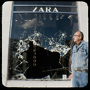 The burned Zara store in Omonia square, Athens <br /> <br /> Following the murder of a 15 year old boy, Alexandros Grigoropoulos, by a policeman on 6 December 2008 widespread riots, protests and unrest followed lasting for several weeks and spreading beyond the capital and even overseas<br /> <br /> When I walked in the streets of my town the day after the riots I instantly forgot the image I had about Athens, that of a bustling, peaceful, energetic metropolis and in my mind came the old photographs from WWII, the civil war and the students uprising against the dictatorship. <br /> <br /> Thus I decided not to turn my digital camera straight to the destroyed buildings but to photograph through an old camera that worked as a filter, a barrier between me and the city.