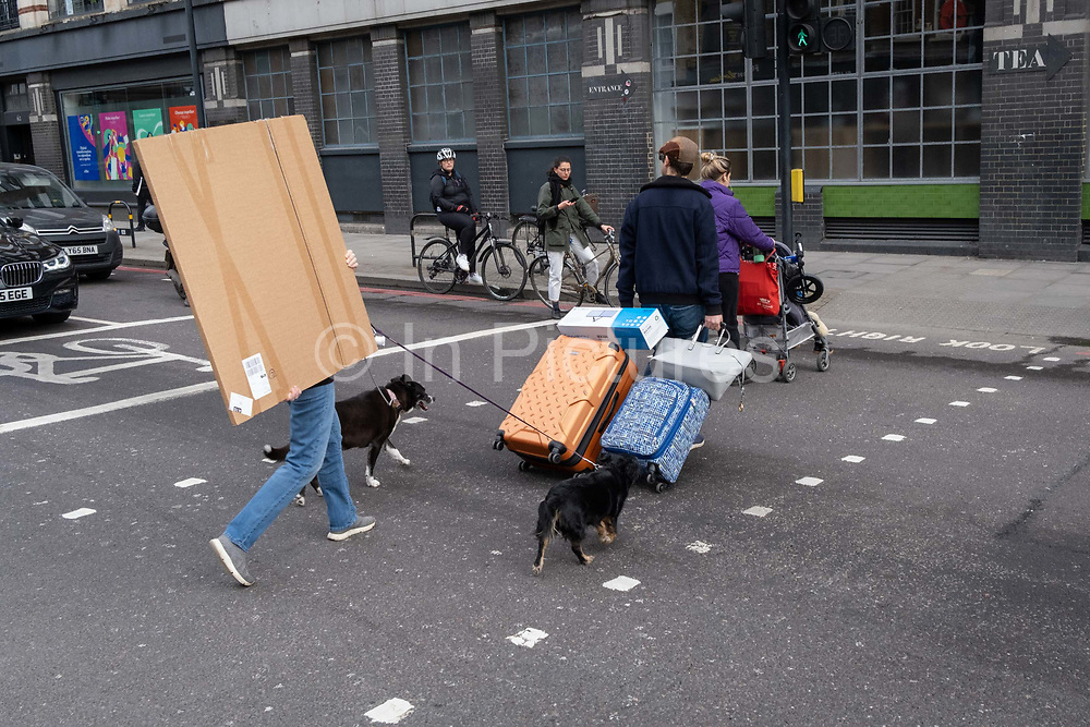 A pedestrian walking two dogs carries a wrapped square item across the road in Hoxton, on 24th February 2021, in London, England.
