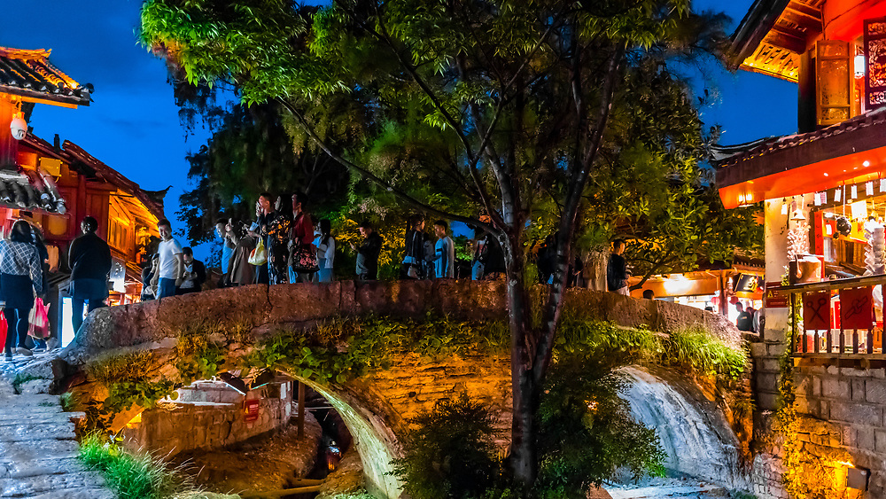 People cross over an ancient stone bridge in Dayan (OLd Town), Lijiang, Yunnan Province, China. The Old Town is a UNESCO World Heritage Site.