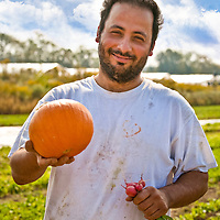 Alvaro Venturelli of Plan B Organic Farm holding a small perfect pumpkin.
