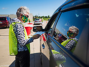29 MAY 2020 - DES MOINES, IOWA: PHYLLIS JOHNSON, a volunteer, checks people in during a produce distribution in a mall parking lot in Des Moines. The Des Moines Area Religious Council (DMARC) and Capitol City Fruit from Norwalk, IA, gave away 1,800 boxes of fresh produce with a mix of vegetables and fruit. The boxes contain enough produce to feed a family of four for a week. The produce was provided by the USDA Farmers to a Families food program. Because of the COVID-19 pandemic, the unemployment rate in Iowa hit 10.2% in May, the highest unemployment rate ever recorded in Iowa and food insecurity in Iowa is impacting communities throughout the state.          PHOTO BY JACK KURTZ