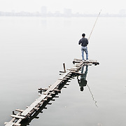 A fisherman stands on a narrow wooden jetty to cast his line on West Lake (Ho Tay) in Hanoi, Vietnam. The thick haze obscures the far shore. Like most of the lakes in Hanoi, West Lake is heavily polluted, which makes the fish caught there of questionable quality for eating.