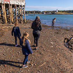 A family explores the shoreline in Lubec, Maine. Mullholland Point Light is across Lubec Narrows on Campobello Island.