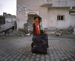 A young boy holds a bag of donated clothes in a badly damaged area of Beit Hanoun, which was mistakenly hit by Israeli airstrikes, Gaza Strip, Palestinian Territories, Nov. 24, 2006. According to Human Rights Watch, since September 2005, Israel has fired about 15,000 rounds at Gaza while Palestinian militants have fired around 1,700 back.