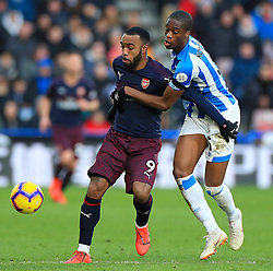 Arsenal's Alexandre Lacazette (left) and Huddersfield Town's Terence Kongolo battle for the ball during the Premier League match at the John Smith's Stadium, Huddersfield.
