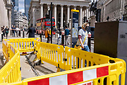 Pedestrians walk around the disruption caused by yellow roadworks barriers, set up on the pavement by street contractors Riney at Bank, in the City of London, the capitals financial district, on 27th May 2021, in London, England.