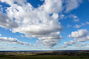 Lines of cumulus clouds in blue sky passing over countryside, Calne, Wiltshire, England, UK