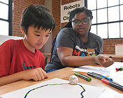 Taisei Tseng, 10, a fourth grade student (left), and Khalia Rucker, a Magic House intern, at the Robots & Circuits station. The small Ozobot follows the special color-coded path Taisei had drawn on the paper, and spins and flashes it's lights based on the colors he drew. The Magic House had two fourth-grade classes from the New City School visit their new permanent satellite location at 5127 Delmar Boulevard in St. Louis, MO on Wednesday May 23, 2019.<br /> Photo by Tim Vizer