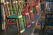 upturned colourful chairs and tables in garden cafe