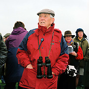 Spectator wearing binoculars standing by the betting kiosks at the Tiverton Staghounds point-to-point steeplechases at Bratton Down, Barnstaple, Devon, UK. Fundraiser for the Devon and Somerset Staghounds.